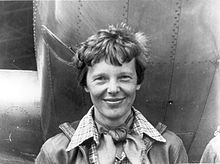 Amelia_Earhart_standing_under_nose_of_her_Lockheed_Model_10-E_Electra,_small